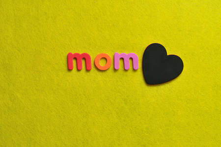 The word mom with a black heart on a yellow background Stock Photo