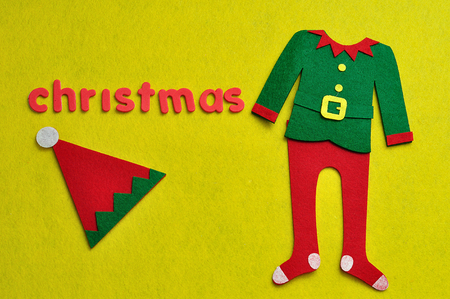 An elf's hat, jacket and pants displayed with the word christmas on a yellow background Stock Photo