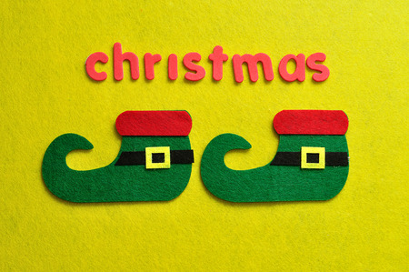 An elf's shoes displayed with the word christmas on a yellow background Stock Photo