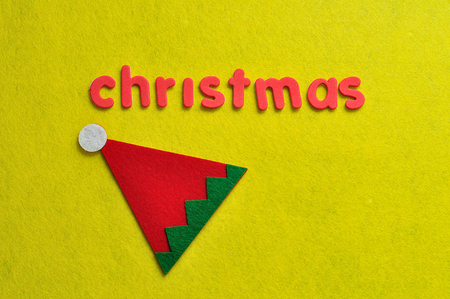 An elf's hat displayed with the word christmas on a yellow background