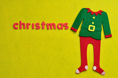 An elf's jacket and pants displayed with the word christmas on a yellow background Stock Photo