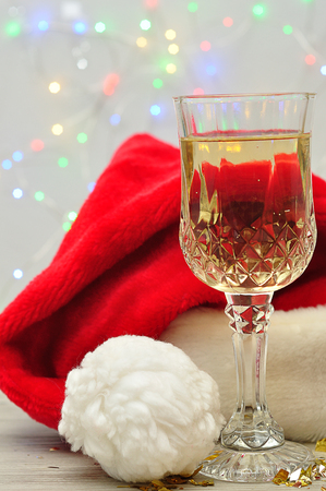 A glass of champagne displayed with a Santa hat and out of focus lights