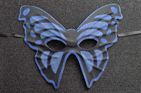 A blue and black mask in the shape of a butterfly
