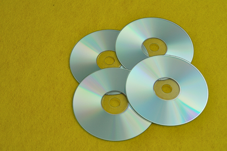 Four cds on a yellow background