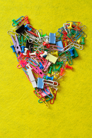 Colorful paperclips, folding clips, push pins and a pegs on a yellow background Stock Photo