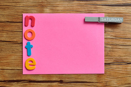 A pink note with the word note and a peg attached with the word saturday on it