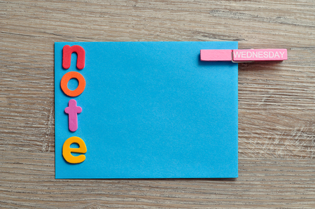 A blue note with the word note and a peg with the word Wednesday attached to it