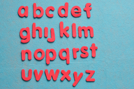 The alphabet in red letters against a blue background Stock Photo