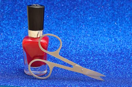 Red nail polish and a nail scissor