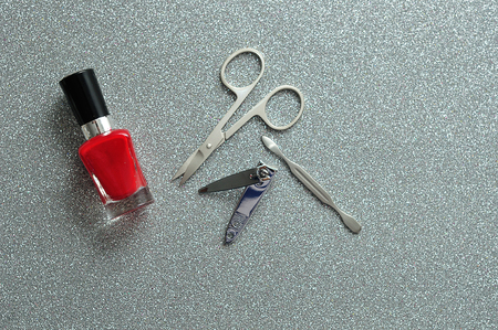 Red nail polish and accessories against a silver background