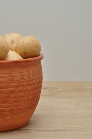 Potatoes in a brown container on top of a table