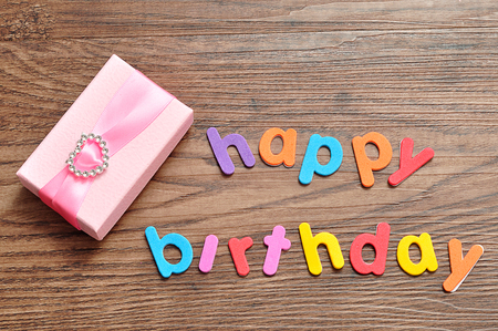Happy birthday in colorful letters with a pink gift box Stockfoto