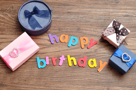 Happy birthday in colorful letters with a variety of gift boxes