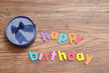 Happy birthday in colorful letters with a blue gift box