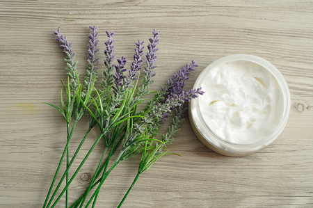 A bunch of lavender displayed with a container white body lotion