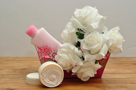 A pink basket filled with body lotion and artificial roses