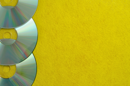A row of Cds on a yellow background Stock Photo