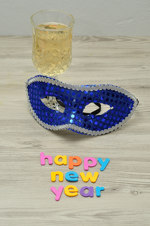 A mask, glass champagne and the words happy new year
