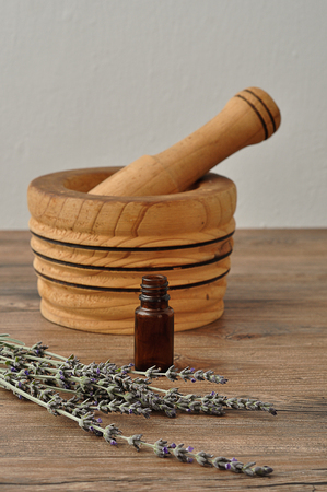 A bunch of lavender displayed with a wooden pestle and a small brown bottle Stock Photo