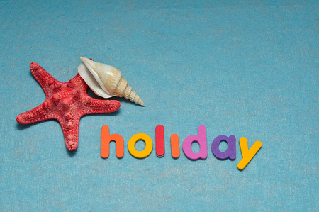A starfish and a sea shell displayed with the word holiday Stock Photo