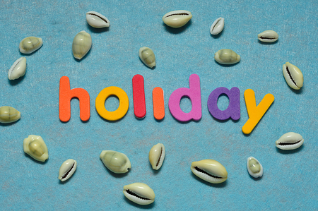Sea shells displayed with the word holiday