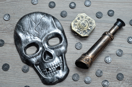 A skull mask, compass and an eyeglass with toy pirate coins