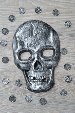 A skull mask with toy pirate coins