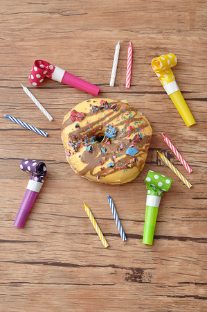 A doughnut displayed with birthday candles and party blowers