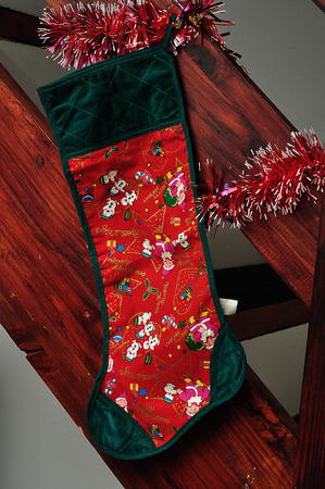 A christmas stocking hanging on the side of wooden stairs