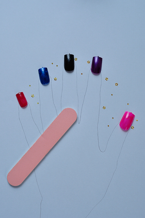 A hand shape with artificial nails in different colors and a nail file Stock Photo