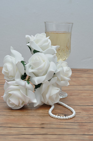 A glass of champagne, white roses and a string of pearls