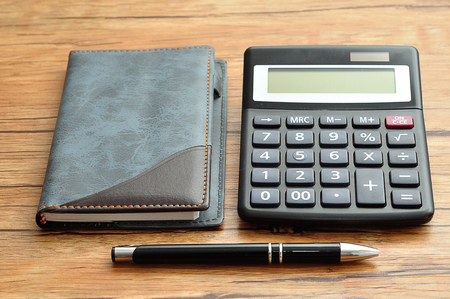 A calculator displayed with a notebook and a pen Stock Photo