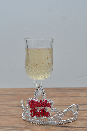 A tiara with the words bride to be displayed with a glass of champagne