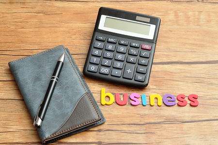 A calculator displayed with a notebook and a pen and the word business