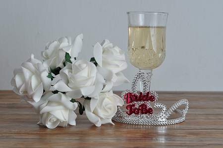 A tiara with the words bride to be displayed with a glass of champagne and white roses