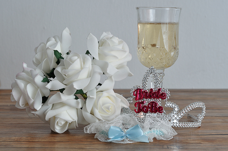 A tiara with the words bride to be displayed with a glass of champagne, white roses and a garter