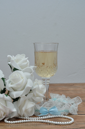 A glass of champagne, white roses, a string of pearls and a garter