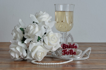 A tiara with the words bride to be displayed with a glass of champagne, white roses and a string of pearls Stock Photo