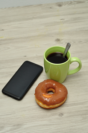 A cellphone, doughnut and cup of coffee Stock Photo