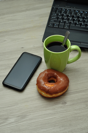 A cellphone, laptop, doughnut and cup of coffee