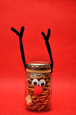 A jar decorated as a reindeer filled with pretzels
