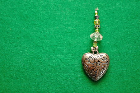 A decorated steel heart on a green background Banco de Imagens