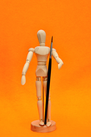 A wooden mannequin display with a paint brush Stock Photo