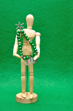 A wooden mannequin display with a christmas tree made out of wire and beads