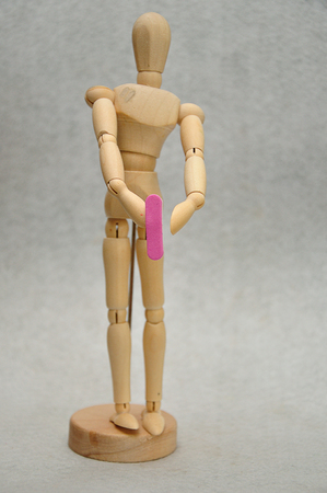 A wooden mannequin holding a letter l