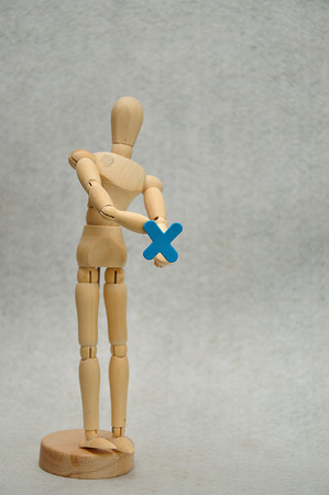A wooden mannequin holding a letter x Stock Photo