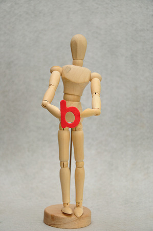 A wooden mannequin holding a letter b Stock Photo