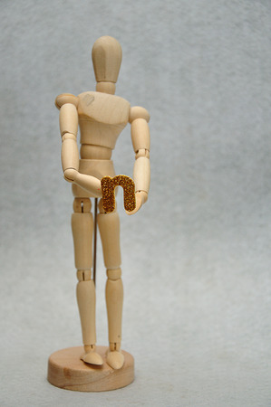 A wooden mannequin holding a letter n