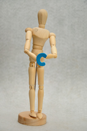 A wooden mannequin holding a letter c