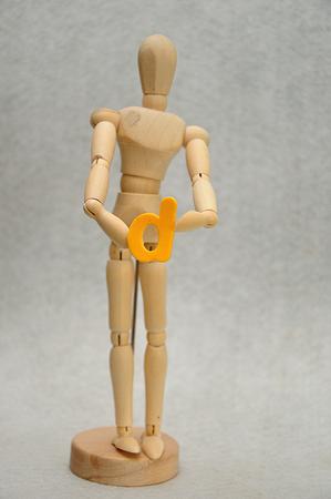 A wooden mannequin holding a letter d